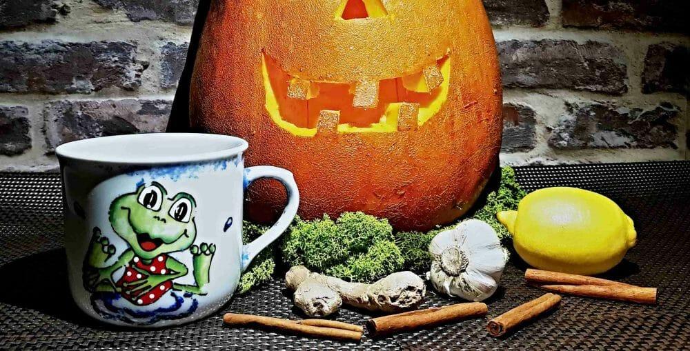 Imunita a jej podpora. Vyrezaná tekvica, horúci čaj v poháriku s motívom žabky, zázvor, škorica, citrón, cesnak.