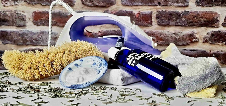 prírodné čistiace prostriedky, sóda na tanieriku, kefa, v pozadí žehlička, v popredí rozsypaná levanduľa